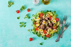 Warm salad from chicken liver, avocado, tomato and quail eggs. Healthy dinner. Dietary menu. Flat lay. Top view Royalty Free Stock Images