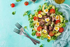 Warm salad from chicken liver, avocado, tomato and quail eggs. Healthy dinner. Dietary menu. Flat lay. Top view Royalty Free Stock Photos