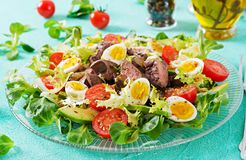 Warm salad from chicken liver, avocado, tomato and quail eggs. Healthy dinner. Dietary menu Royalty Free Stock Photo