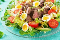 Warm salad from chicken liver, avocado, tomato and quail eggs. Healthy dinner. Dietary menu Stock Photo