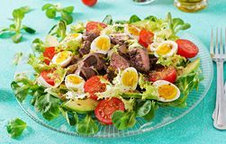 Warm salad from chicken liver, avocado, tomato and quail eggs. Healthy dinner. Dietary menu Royalty Free Stock Photos