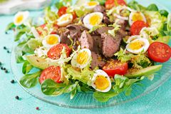 Warm salad from chicken liver, avocado, tomato and quail eggs. Healthy dinner. Dietary menu Stock Image