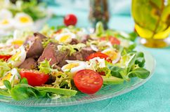 Warm salad from chicken liver, avocado, tomato and quail eggs. Healthy dinner. Dietary menu Stock Photos