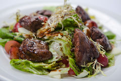 Warm salad with chicken liver and grapes. On the white plate Royalty Free Stock Images