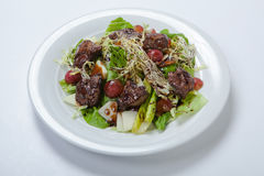 Warm salad with chicken liver and grapes Stock Photos