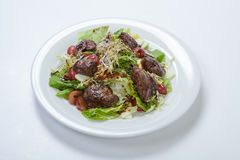 Warm salad with chicken liver and grapes. On the white plate Stock Image