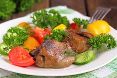 Warm salad with chicken liver, sweet peppers, cherry tomatoes and salad mix.  Royalty Free Stock Photo