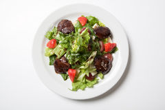 Warm salad with chicken liver. On a white plate Stock Image
