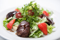 Warm salad with chicken liver. On a white plate Stock Images