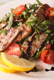 Warm salad of grilled beef with arugula and tomatoes macro. vert Stock Photography
