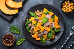 Warm salad with pumpkin, baked beef, spinach and chickpeas. Top view on black background. Healthy food Stock Photos