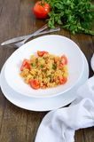 Warm salad with seafood in a white bowl on a wooden background. Royalty Free Stock Image