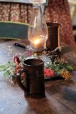 Warm scene with old fashioned lamp and Christmas wreath with coffee cup on wood table stock photo