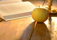 Warm scene with open book and apple. Open book and an apple on a wooden table with a beautiful warm light shining on them Stock Photo