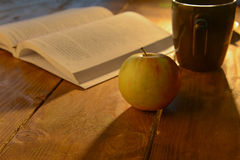 Warm scene with open book and apple. Open book and an apple on a wooden table with a beautiful warm light shining on them Royalty Free Stock Photography