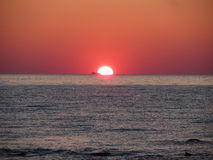 Warm sea sunset with cargo ship in the background Stock Photo
