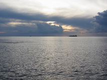 Warm sea sunset with cargo ship at the horizon . Giants cumulonimbus clouds are in the sky. Tuscany, Italy Stock Image