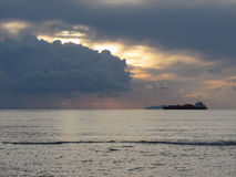 Warm sea sunset with cargo ship at the horizon . Giants cumulonimbus clouds are in the sky. Tuscany, Italy Stock Photo