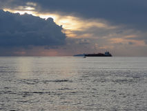 Warm sea sunset with cargo ship and a small fishing boat at the horizon . Giants cumulonimbus clouds are in the sky. Tuscany, Ital Stock Images