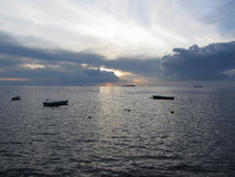 Warm sea sunset with cargo ships and small fishing boats at the horizon . Giants cumulonimbus clouds are in the sky. Tuscany, Ital Royalty Free Stock Images