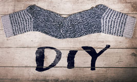 Warm selfmade wool socks on wooden table, word diy. Do it yourself Stock Photos