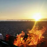 Warm Settings. Sunset on the beach with a bonfire Royalty Free Stock Image