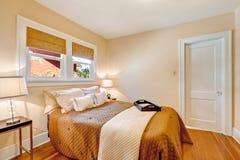 Warm slaapkamerbinnenland met bruine beddegoed en ivoordeken Stock Afbeeldingen