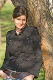 Warm Smile 5. Young woman sitting beneath a tree smiling Royalty Free Stock Photo