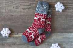 Warm socks. Warm colored socks with ornaments and white snowflakes are on the table royalty free stock image