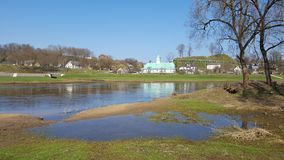 Warm spring in the town. Near the river. A mound and church near the river stock image