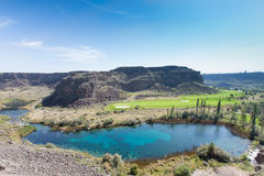 Warm springs and tranquil lake, Jerome, Idaho. Warm springs and tranquil blue lake, Jerome, Idaho with lush green farmland in the valley between rugged mountain Stock Images