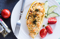 Warm stuffed zucchini with chicken and vegetables on a white pla Stock Images