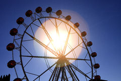 Warm summer day at the carnival. With ferris wheel, sun flare Royalty Free Stock Photo