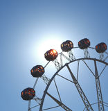 Warm summer day at the carnival. With ferris wheel, sun flare Stock Photography