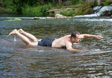 A young man is swimming on a very shallow river, he is funny and cheerful. Warm summer day, rest on the nature. A young man is swimming on a very shallow river Stock Image