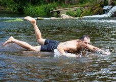 A young man is swimming on a very shallow river, he is funny and cheerful. Warm summer day, rest on the nature. A young man is swimming on a very shallow river Stock Photo