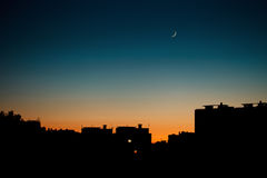 A warm summer evening in the city. Cityscape silhouette with the moon royalty free stock photos