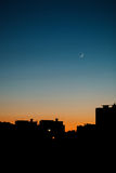 A warm summer evening in the city. Cityscape silhouette with the moon royalty free stock photo