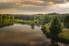 Warm summer evening. a view of the river with grassy coasts, trees and a dense forest under a cloudy sky. Warm summer evening. beautiful view of the river with stock photo