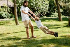 Warm sunny day. Cheerful little boy with his father in white t shirts are playing outdoor. Father is circling son around stock photos