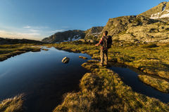 Warm sunrise in the Alps. Male hiker with backpack and stick taking rest and watching sunrise near lake and stream in the italian Alps Stock Photos