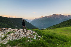 Warm sunrise in the Alps. Male hiker taking rest and watching sunrise in the italian - french Alps on grassy landscape overlookign the valleys below Royalty Free Stock Photo