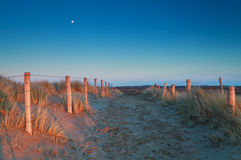 Warm sunset light and moon over sand path Royalty Free Stock Photography