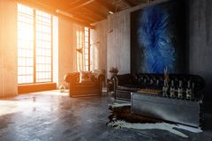 Polished concrete living room with bright windows. Warm sunset light streams through tall windows illuminating a contemporary, industrial polished concrete Royalty Free Stock Image