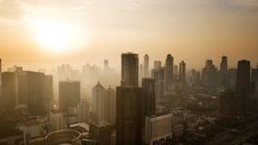 Warm sunset over downtown Jakarta. JAKARTA - Indonesia. May 21, 2018: Warm sunset over skyscrapers in downtown Jakarta Royalty Free Stock Photos
