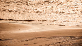 Warm sunset on the sand beach. Warm sunset on a textured sand beach with little waves on the sea Stock Images