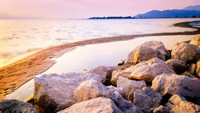 Warm sunset on the sand beach with rocks in front Stock Photos