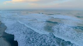 Warm sunset sunrise over calm white foamy wave of Cocoa Beach shore coast line Florida Atlantic ocean in 4k aerial drone. Warm sunset sunrise over calm white stock footage