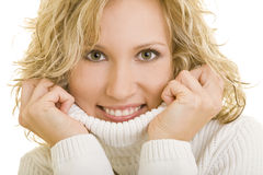 Warm sweater. Young blond woman holding the turtleneck of her white sweater royalty free stock photos