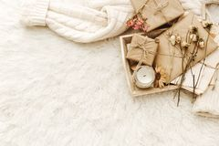 Warm sweater, craft paper, present and dried flowers at white background. Cozy vintage. Flat lay, top view stock images